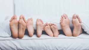 stopy całej rodziny lezacej w lozku